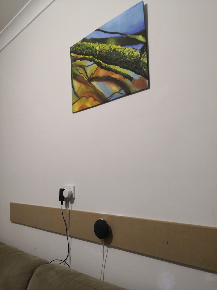 A small Google Home device attached to a wall under a piece of art
