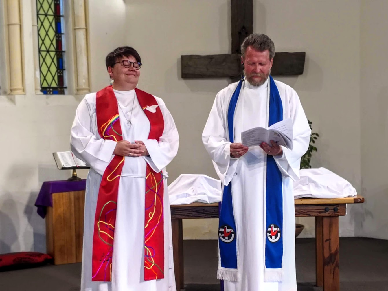 Carlynne standing in her alb and stole with another minister during her ordination ceremony