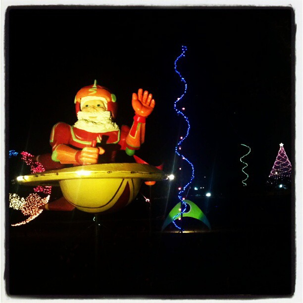 A night photo of a big anamatronic Santa in a space ship
