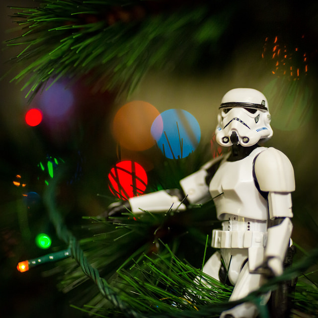 A photo of a Star Wars Stormtrooper toy in a Christmas tree with twinkling lights behind