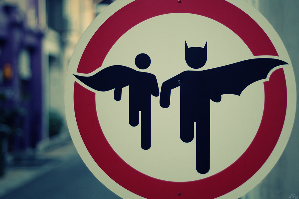 A parking zone sign with Batman and Robin silhouettes